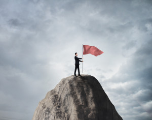 businessman standing on rock with red flag